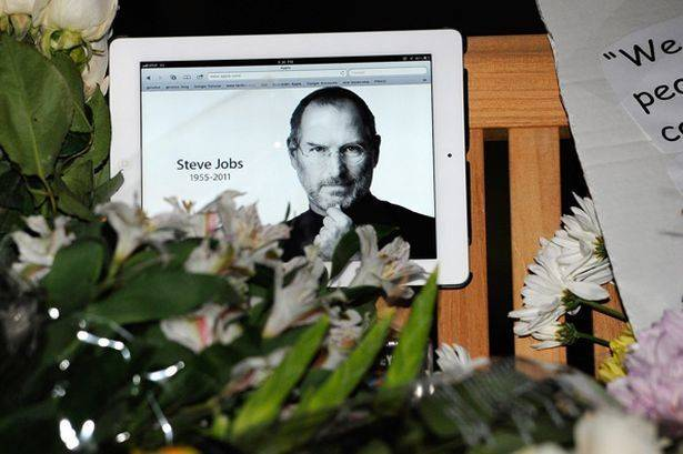 flowers-and-an-ipad-showing-a-picture-of-steve-jobs-are-placed-at-a-makeshift-memorial-276242920.jpg
